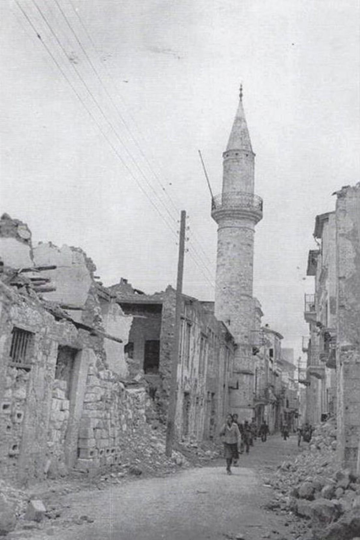 1941, οδός Χατζημιχάλη Νταλιάνη μετά τους βομβαρδισμούς. Ο μιναρές και το τζαμί του Αγά Χαν παραμένουν ανέπαφα.