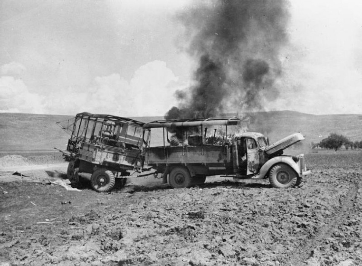 Battle for Crete. 31 MAY 1941. A British lorry and trailer burning after being attacked by Luftwaffe aircraft