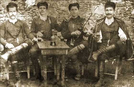 Cretans at a get-together with a fiddler, ealy 20th