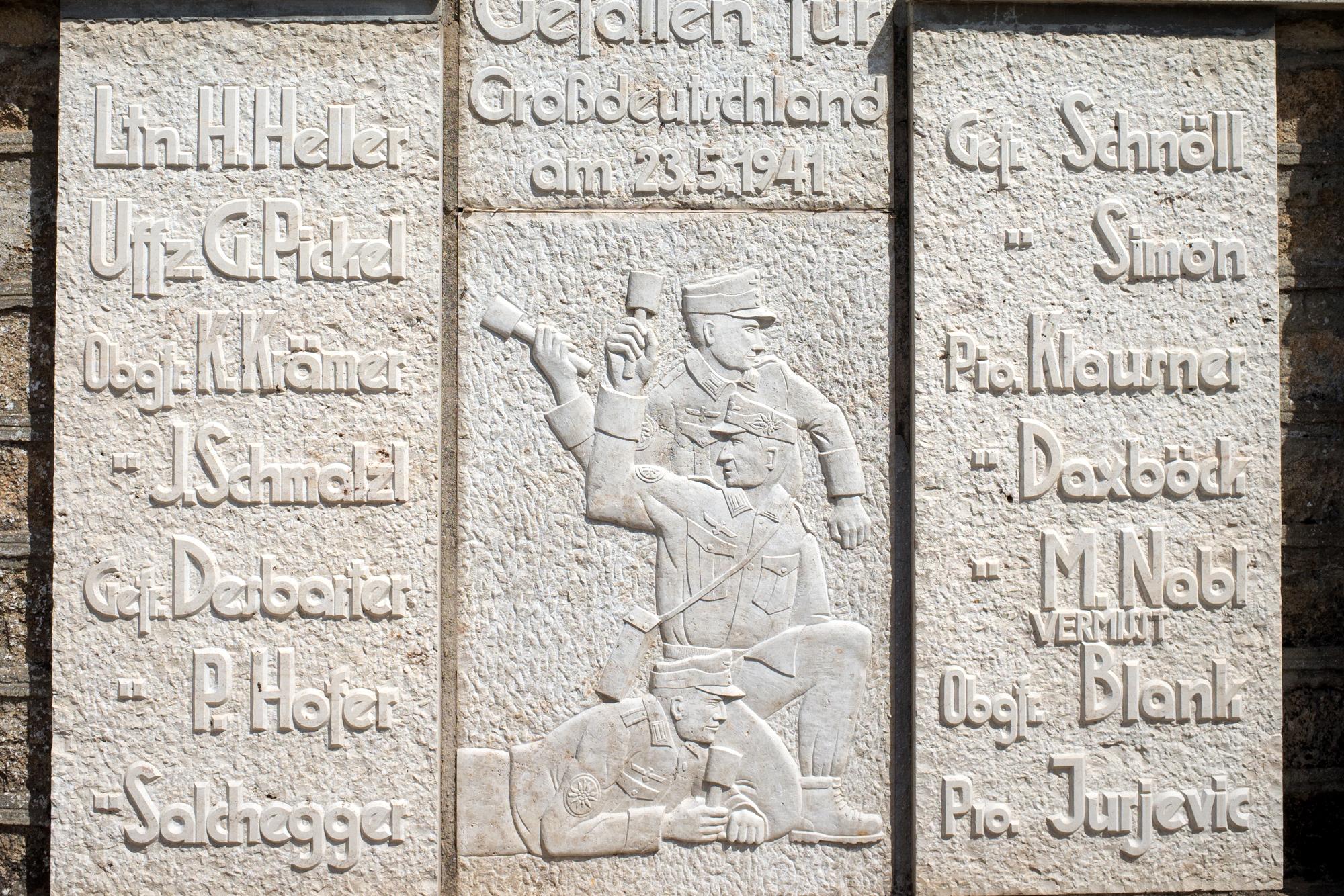 """Στο ανάγλυφο στο μνημείο οι στρατιώτες της Βέρμαχτ φορώντας τις χαρακτηριστικές στολές με το σήμα """"εντελβάις"""" της 1ης Μεραρχίας είναι έτοιμοι να πετάξουν χειροβομβίδες"""